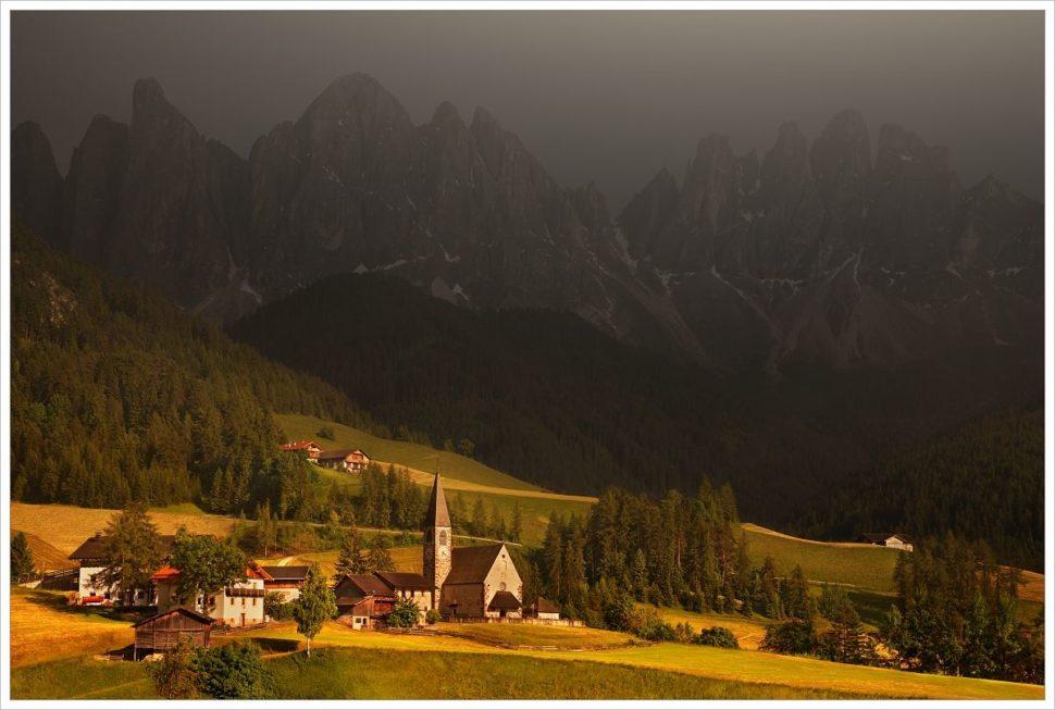 Bouřková atmosféra a posledním sluncem nasvícený kostel v údolí Val di Funs- fotografický workshop Rozkvetlé letní Dolomity