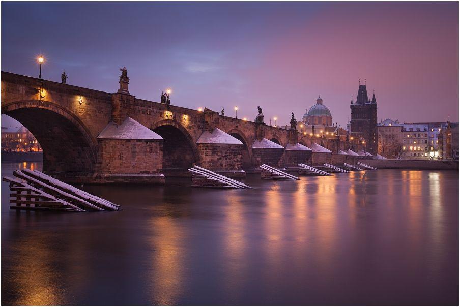 Pohled na mlhavý a světly nasvícený Karlův most v historické části Prahy