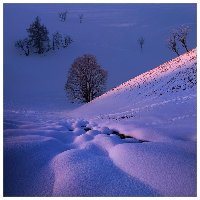 Krušné hory-zasněžená krajina vmodré hodince stypickými modro fialovými tóny